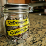 retirement_savings_money_jar-_a_clear_glass_jar_filed_with_coin
